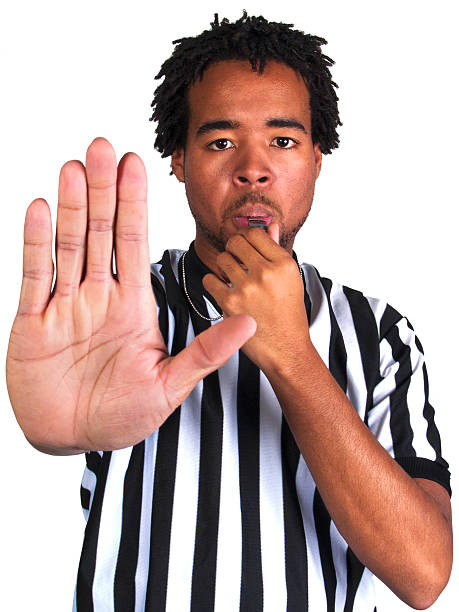 black male referee blowing a whistle and gesturing stop - judge sports official stock photos and pictures