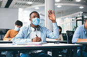 istock Black male student raising hand, wearing medical mask 1286520540
