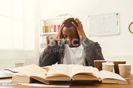 istock Black male student studying at table full of books 936144548