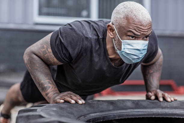 A black male working out wearing a face mask during virus outbreak stock photo