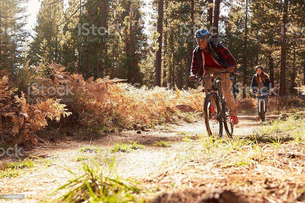 Black man and Caucasian woman riding bikes on a forest stock photo