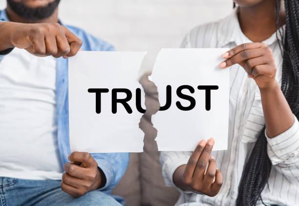 schwarzer mann und frau reißen papier mit vertrauen inschrift - trust stock-fotos und bilder