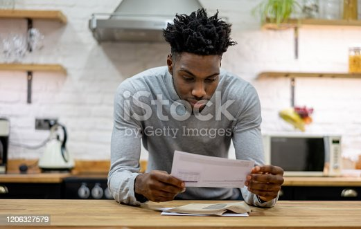 Portrait of a black man at home reading the mail - lifestyle concepts
