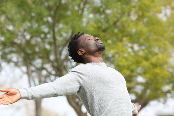 Black man breathing fresh air stretching arms in a park Black man breathing fresh air stretching arms in a park with a green tree in the background deep stock pictures, royalty-free photos & images