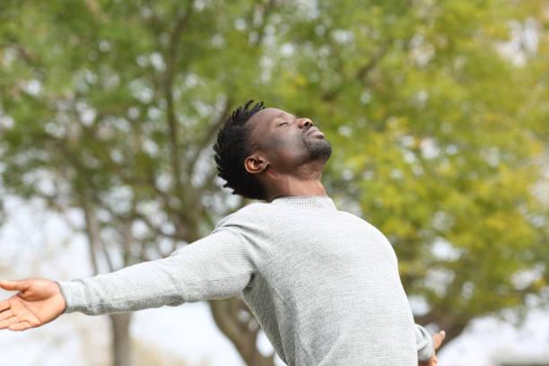 homem negro respirando ar fresco esticando os braços em um parque - consciencia negra - fotografias e filmes do acervo