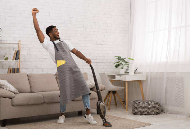 Black man cleaning house with wireless vacuum cleaner Yeah, I did it. Excited african-american man celebrating achievement while cleaning house with wireless vacuum cleaner, copy space cleaning equipment stock pictures, royalty-free photos & images