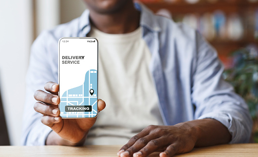 Black Man Demonstrating Smartphone With Opened Delivery Service Tracking App On Screen, Enjoying Modern Technologies For Logistic And Shipping, Creative Collage, Cropped Image