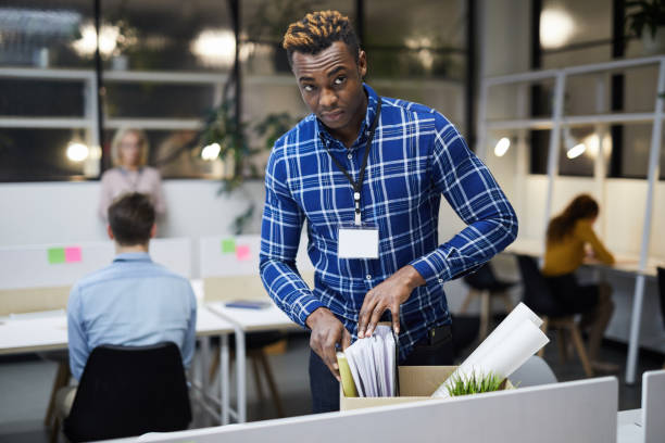 Black man discharged from place of employment Serious frowning young black man with badge on neck discharged from place of employment checking paper files in box while leaving office quitting a job stock pictures, royalty-free photos & images