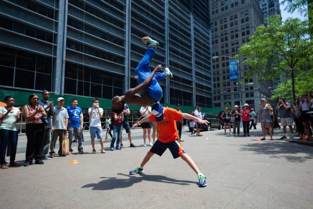 A black man doing a somersault over a tourist in Lower Manhattan - foto de stock