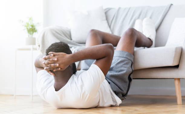 Schwarzer Mann macht Bauchtraining und knirscht im Wohnzimmer – Foto