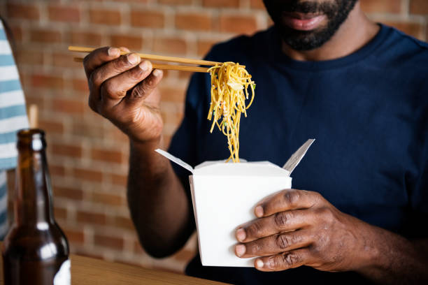 Black man eating Chow mein Black man eating Chow mein chinese takeout stock pictures, royalty-free photos & images