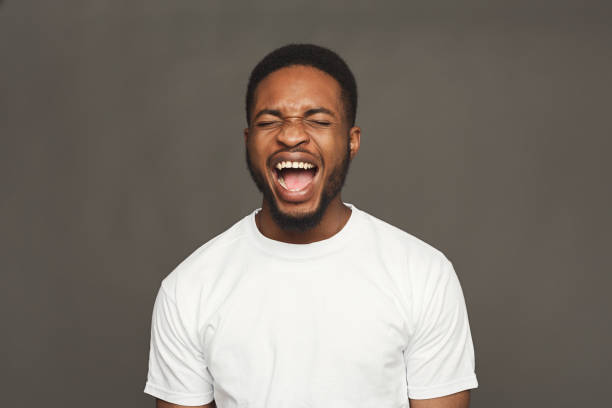 Black man expressing anger, feeling furious, shouting stock photo