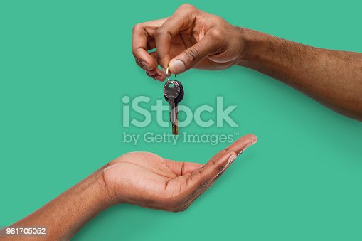 istock Black man handing key over to person hand 961705052