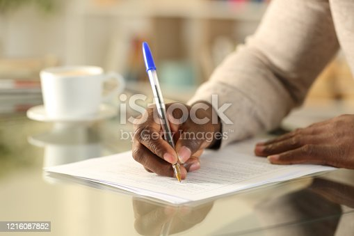 Close up of a black man hands filling out form on a desk at home