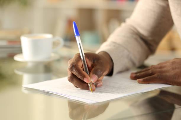 черный человек руки заполнения формы на столе - писать стоковые фото и изображения