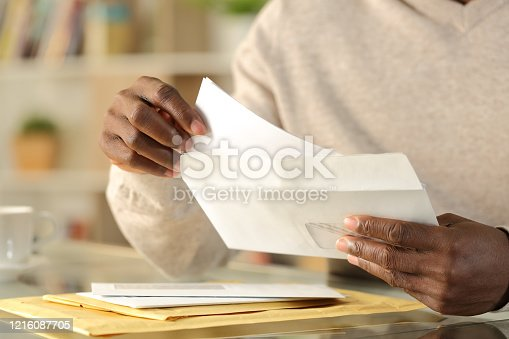 Close up of black man hands putting a letter inside an envelope on a desk at home