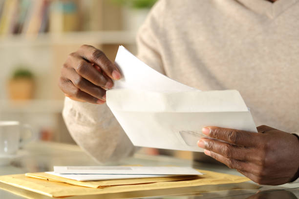 Black man hands putting a letter inside an envelope Close up of black man hands putting a letter inside an envelope on a desk at home note message stock pictures, royalty-free photos & images