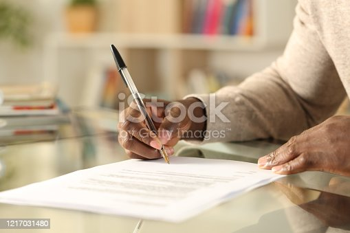 istock Black man hands signing document on a desk at home 1217031480