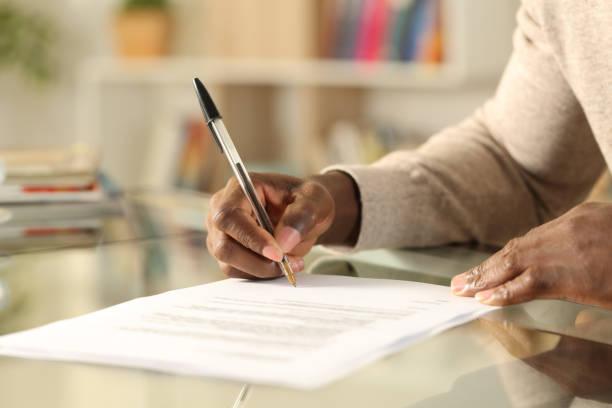 schwarzer mann übergibt unterschriftsdokument auf einem schreibtisch zu hause - unterschrift stock-fotos und bilder