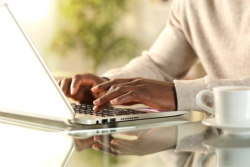 Close up of black man hands typing on a laptop sitting on a desk at home