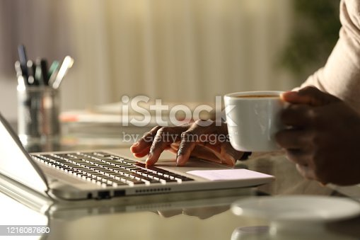 Close up of a black man hands using laptop holding a coffee cup in the night on a desk at home