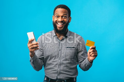 1173546354 istock photo Black man holding credit card and cellphone at studio 1251669850
