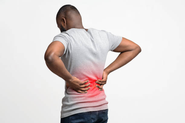 Black man holding his hands on lower back Afro guy holding both hands on lower back, pain in spine, inflamed zone highlighted in red, white background, free space back pain stock pictures, royalty-free photos & images