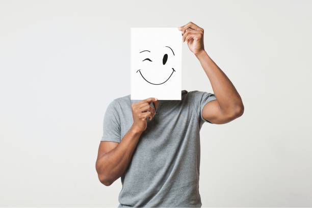 Black man holding paper with smiley face Black man cover his face with happy and winking smiley drawn on paper, white studio background unrecognizable person stock pictures, royalty-free photos & images