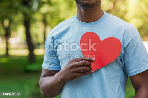istock Black man holding red heart on his chest 1145183163