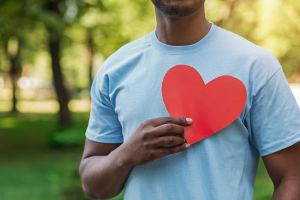 black man holding red heart on his chest - voluntário imagens e fotografias de stock