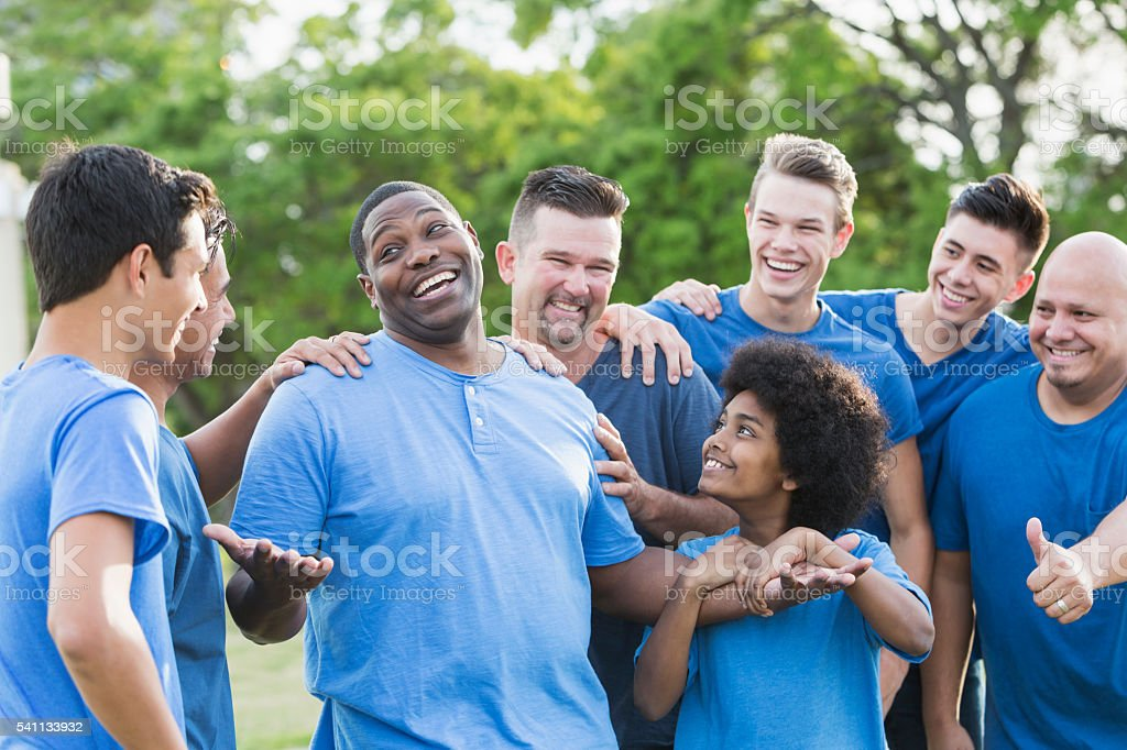 A group of men and sons standing together outdoors in the park...