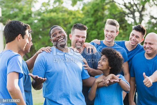 A group of men and sons standing together outdoors in the park wearing blue shirts. An African American man is the center of attention, being congratulated for his accomplishment. They are all part of a team doing a community service project, happy and smiling.