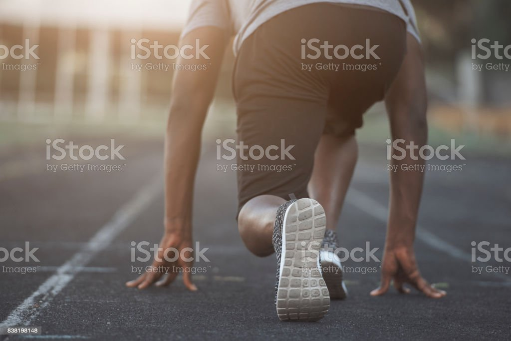 A black man is in starting position before sprinting stock photo