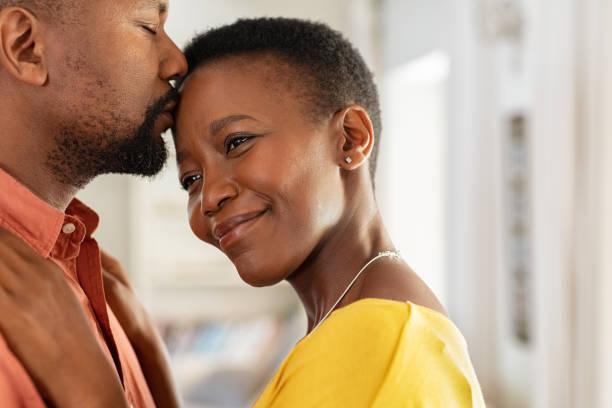 svart man kysser sin fru på pannan - middle aged man dating bildbanksfoton och bilder