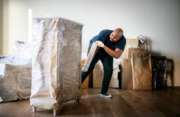 black man moving furniture - avvolgere foto e immagini stock