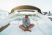A cheerful wealthy bearded mature black guy in an elegant striped black and white costume with shorts and hat is sitting outdoors on the deck of a luxury bright speed yacht moored on a berth