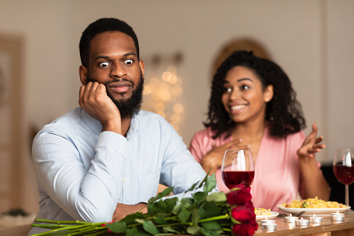 Bad First Impression And Date Concept. Dissatisfied shocked black man listening to excited emotional obsessed woman talking, young couple sitting at table in cafe. Unpleasant conversation