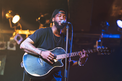A black man is playing the acoustic guitar and singing passionately on stage.