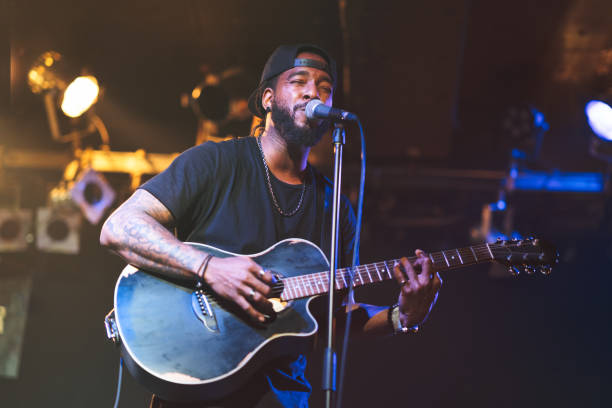 Black man playing acoustic guitar and singing on stage A black man is playing the acoustic guitar and singing passionately on stage. guitarist stock pictures, royalty-free photos & images