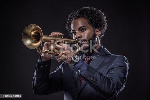 Black Man playing a jazz trumpet wearing an elegant formal suit in a studio shoot