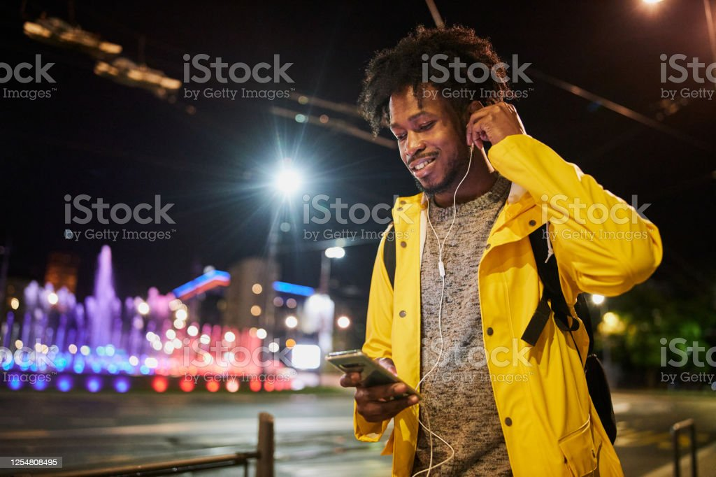 Black man playing music on his phone while walking outdoors Young African American man text messaging and listening to music outdoors while on his night walk Adults Only Stock Photo