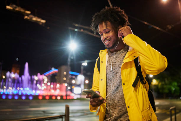 Black man playing music on his phone while walking outdoors stock photo