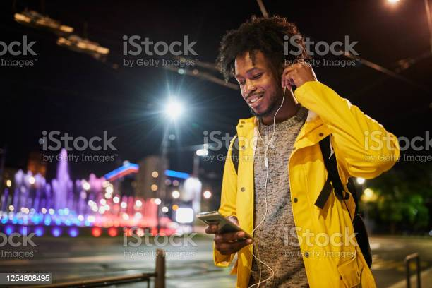 Black Man Playing Music On His Phone While Walking Outdoors Stock Photo - Download Image Now