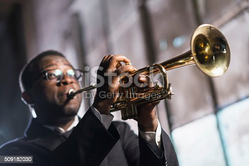 An African American man playing a trumpet.  The musician is wearing a black jacket and tie, performing on stage. It is a low angle view, with the focus on his hands and the musical instrument.