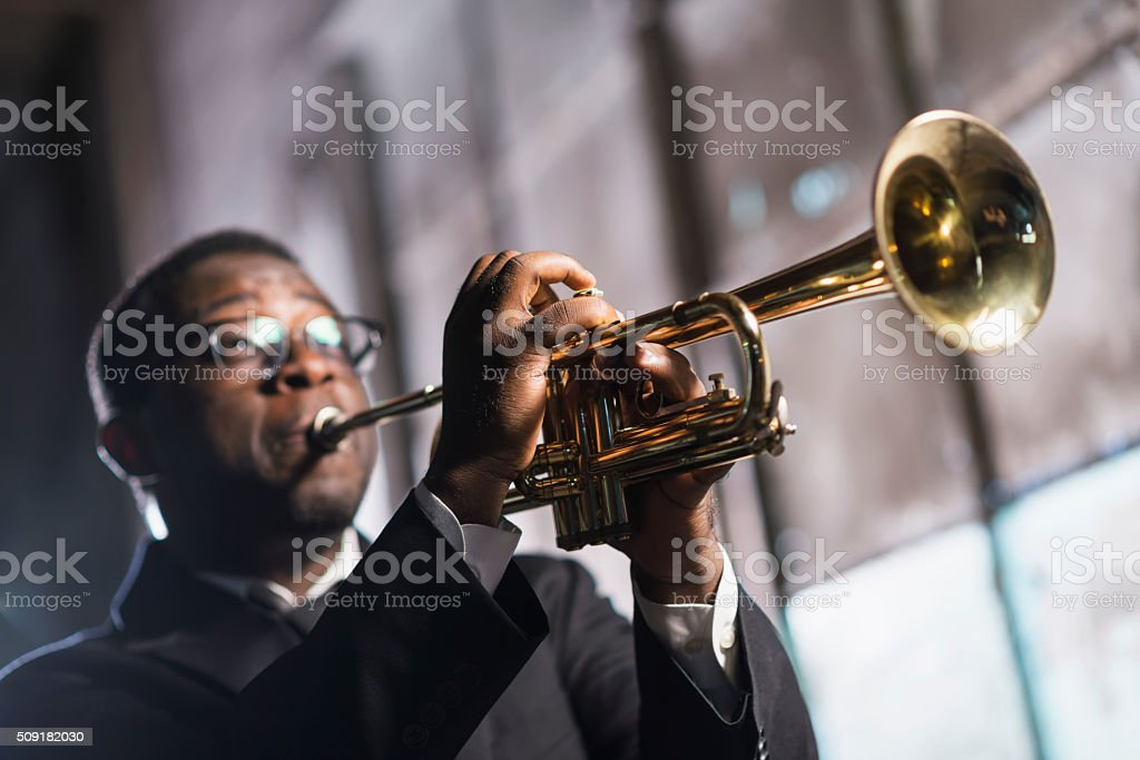 Black man playing trumpet stock photo