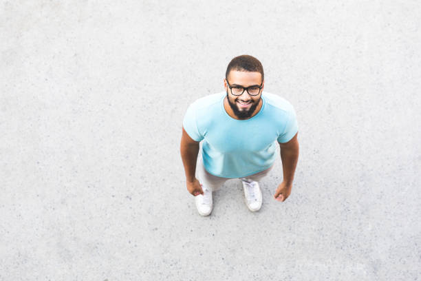 Black man portrait. Over head shot Black man portrait. Over head shot, the man is looking up at camera. He is wearing black eyeglasses and a light blue t-shirt. Smiling man on a concrete pavement directly below stock pictures, royalty-free photos & images