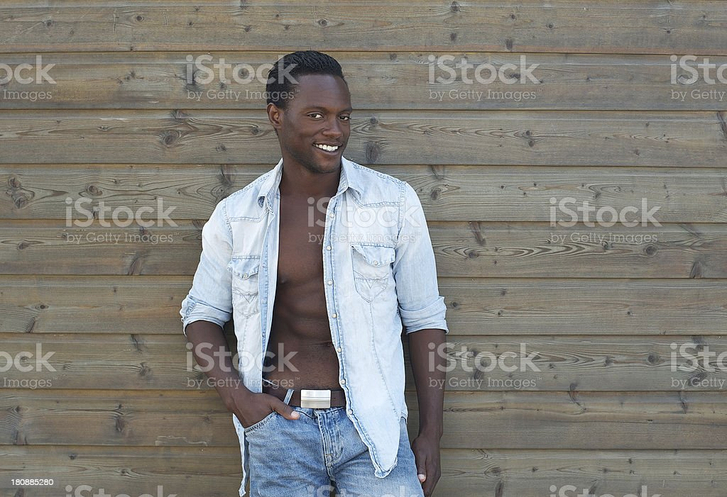 Black man posing outdoors with open shirt stock photo