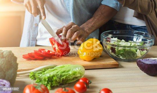 Black man cutting vegetables for healthy vegetarian salad in kitchen, closeup