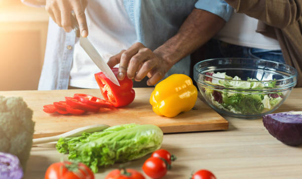 Black man preparing vegetable salad Black man cutting vegetables for healthy vegetarian salad in kitchen, closeup preparing food stock pictures, royalty-free photos & images