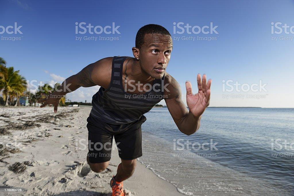 Black Man Running on Beach Marathon Training Outdoors stock photo